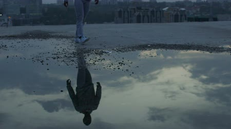 dekarz : Sad man walking alone looking at reflections of gloomy sky in puddles, crisis