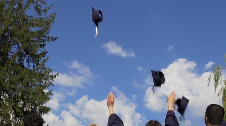 high school : Cheerful students throwing graduate caps into air, rejoicing at studies finish Stock Footage