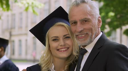 mezun : Happy father proud of his clever daughter graduating from university with honors Stok Video