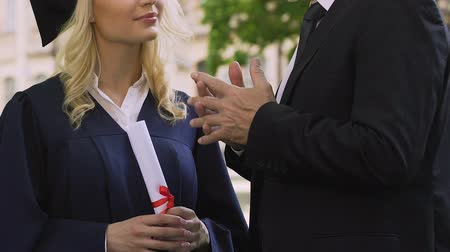 grãos : Teacher gives life instructions to female graduate student in academic dress