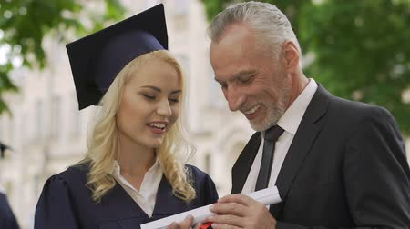attainment : Happy father proud of daughter and congratulating her on education diploma
