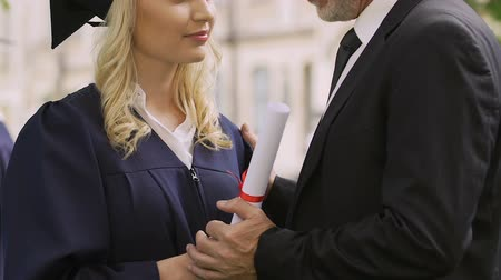 bakalář : Dad praising and congratulating his clever daughter on obtaining diploma