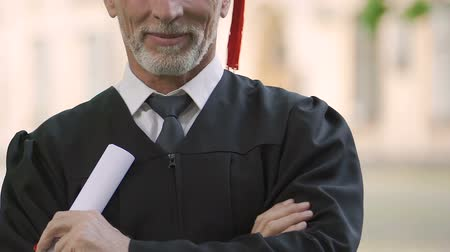 grau : Mature man proud of receiving high school diploma, postgraduate education Stock Footage