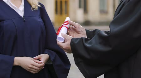 гордый : Dean of faculty expressing gratitude and handing diploma to female student