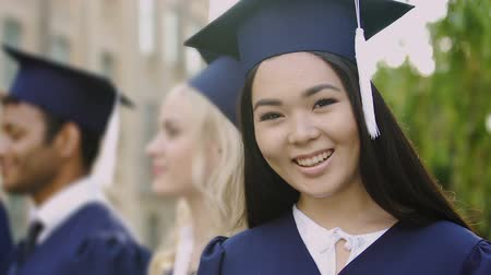 completion : Asian girl in academic dress smiling posing at camera during graduation ceremony Stock Footage