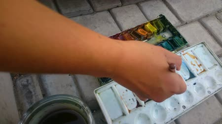 paintbox : Hand of street artist painting with brush and watercolor paints, creative hobby