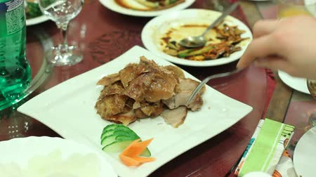 post room : Banquet guest taking appetizing fatty fried meat from dish on restaurant table