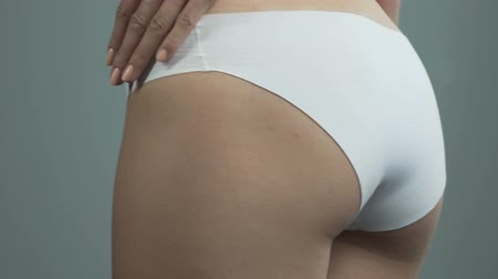 período : Reflection of fit female buttocks in underwear, healthy smooth body, close-up