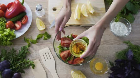 olive oil pour : Close-up of girl adding olive oil into bowl with fresh salad, traditional recipe