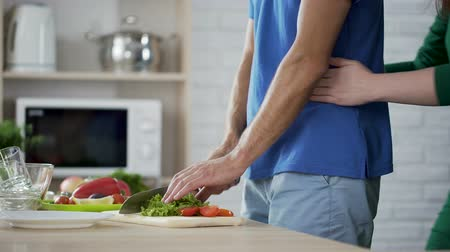 domates : Wife gently hugging her husband who cooking vegetable salad for family lunch Stok Video