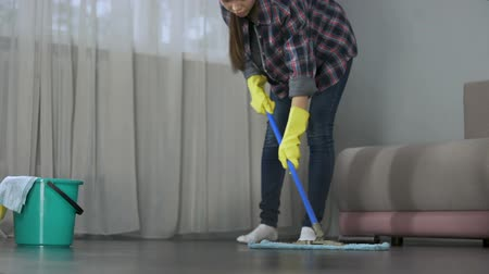 obsessive : Obsessive with cleanliness young lady thoroughly washing floor of her house