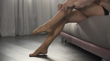 stockings : Elegant woman going on date, putting nylon tights on her beautiful legs Stock Footage