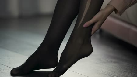 sock : Lady in hurry going to work and accidentally tearing pantyhose, bad start of day Stock Footage