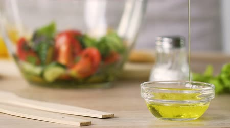 olive oil pour : Chef pouring olive oil to measuring bowl, dressing salad, cooking healthy food Stock Footage