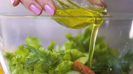 ocet : Female cook pouring olive oil in fresh vegetable salad seasoning it, slow-mo