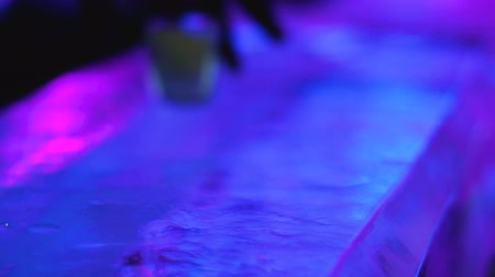 baton : Barman skillfully serving icy glass with shot to client of creative ice bar Wideo