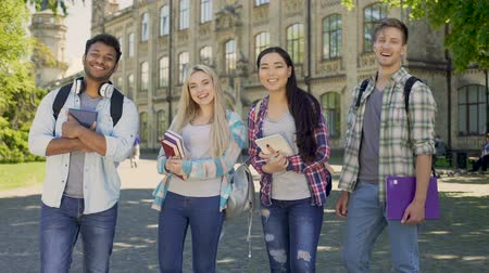 integrovaný : Mixed-race students laughing looking into camera, standing on university campus