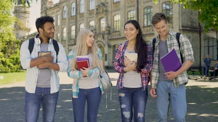 sincerely : Friends joyfully laughing looking at each other, standing near university Stock Footage