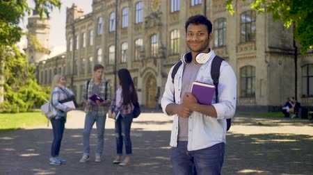 sincerely : Excellent student standing near his university, sincerely smiling at camera Stock Footage