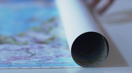 boundary : Person slowly opening world map poster, planning military operation strategy Stock Footage