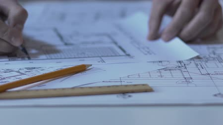 kidolgozása : Male architect checking building layout, making notes and calculations, design