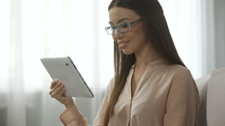 тачпад : Young attractive woman looking into camera with a tablet, satisfied person