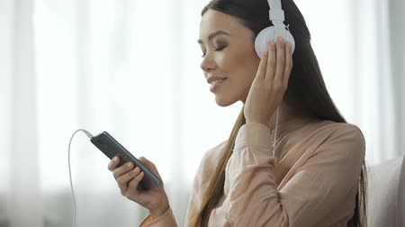 песня : Appealing woman listening music in headphones, loves radio station, enjoyment Стоковые видеозаписи