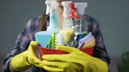 cleaning products : Smiling woman lifting up bucket with numerous household cleaning substances Stock Footage