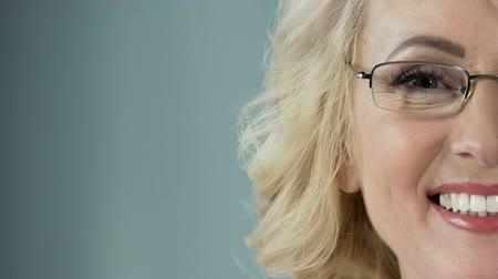 protetyka : Beautiful senior blonde with eyeglasses smiling into camera, health care
