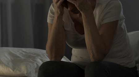 pensão : Depressed mature lady sitting on bed and suffering from headache, health problem
