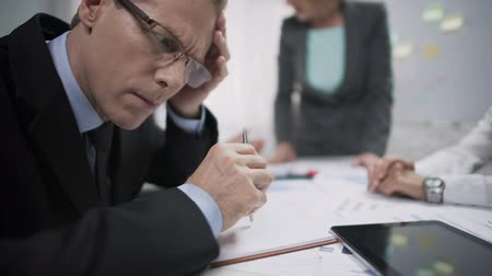 neurotic : Overworked financial manager looking tired during brainstorm with annoyed boss Stock Footage