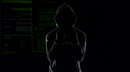 hapis : Silhouette of handcuffed angry hacker on animated computer code background Stok Video