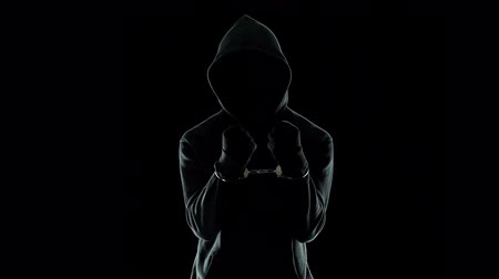 serial : Silhouette of handcuffed male in hoodie, dangerous criminal punished by law