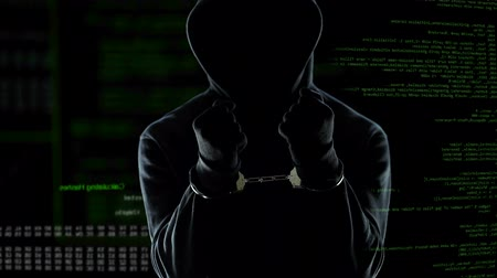 kajdanki : Male hacker with handcuffs standing in front of animated computer code, IT thief