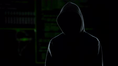 rabló : Unknown hooded male hacker looking into camera, global cybercrime problem