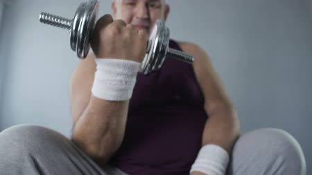 упитанность : Purposeful obese man lifting dumbbells at home, working hard to lose weight