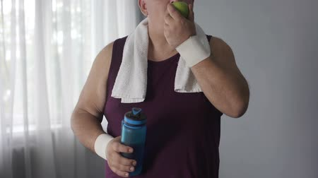 hidratáció : Corpulent male drinking still water and eating green apple after training, diet