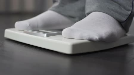 com escamas : Obese man measuring his weight on health scale, dieting and weightloss, close-up