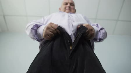 zíper : Base view of overweight man trying hard to zip tight pants, disappointment