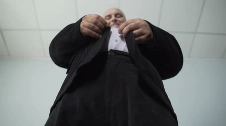 tutturma : Overweight male trying to fasten a button on his jacket, bottom view of fat man Stok Video
