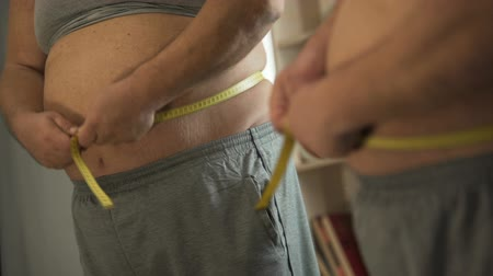 упитанность : Angry man with weight problems measuring his waistline in front of mirror