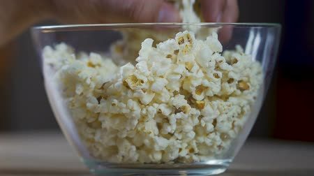 pop corn : Man hands taking popcorn from the glass bowl, watching tv shows and eating Filmati Stock
