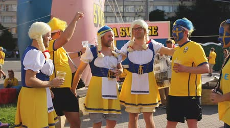 švédský : Happy supporters of Sweden football team posing dressed in funny costumes