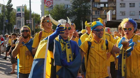 İsveççe : Swedish football fans dressed in funny mascot hats glorifying national team Stok Video