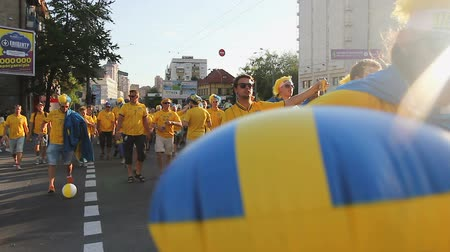 İsveççe : Excited fans of Swedish national football team crossing road loudly chanting