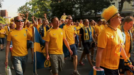 procession : Huge crowd of football fans in national color suits going to stadium team spirit