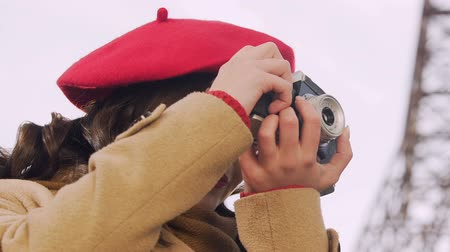 pic : Attractive woman taking photos with camera, looking for a good shot, hobby