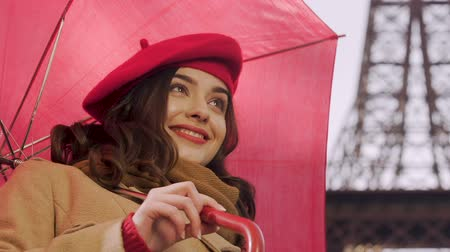 fetching : Young woman with umbrella flirting, looking for acquaintance, smiling to man Stock Footage