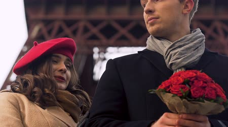 hassaslık : Girl playfully coming behind boyfriend, man with bouquet waiting for woman Stok Video