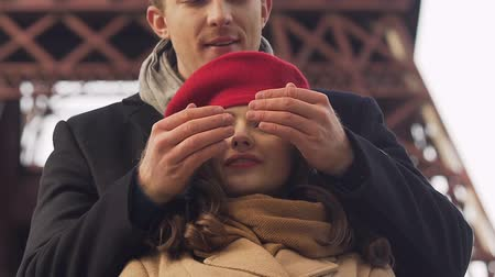 warms : Young man surprises his girlfriend by covering her eyes with hands, happy date